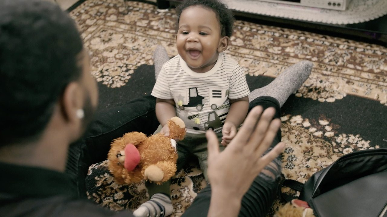 Baby smiling holding a teddy, dad with his hands up.