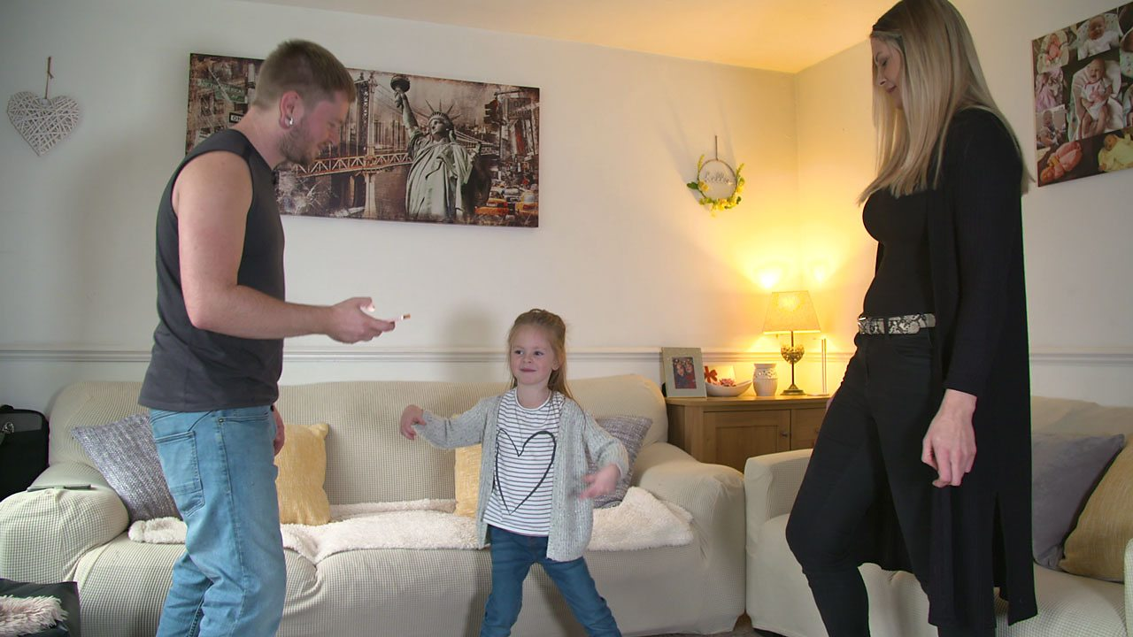 Little girls dancing next to sofa and in between her mum and dad