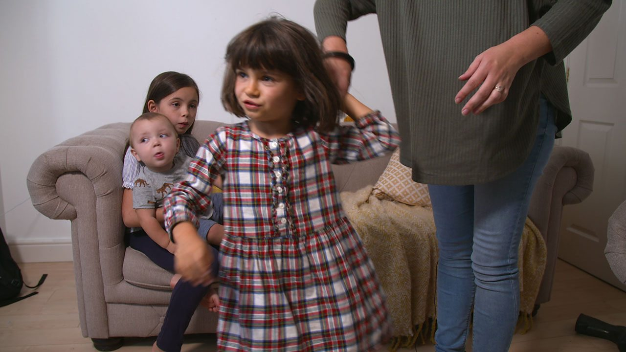 Girl in checked dress holding hands with mum while her family look on from sofa.