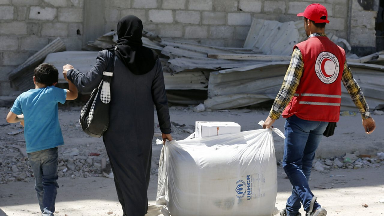 This picture shows a member of the Red Crescent helping a resident of the Syrian town of Douma to carry humanitarian aid.