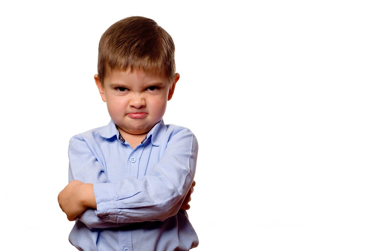 Angry little boy with arms folded