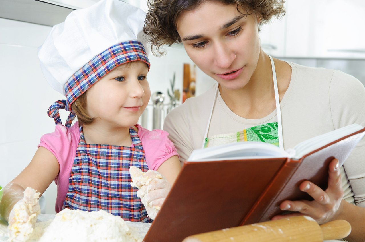 A mother and daughter look at a cookery book