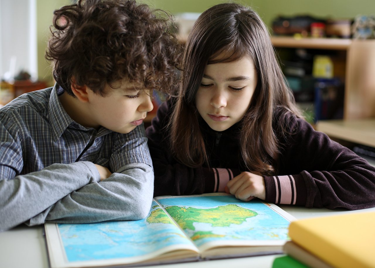 Two children look at an atlas
