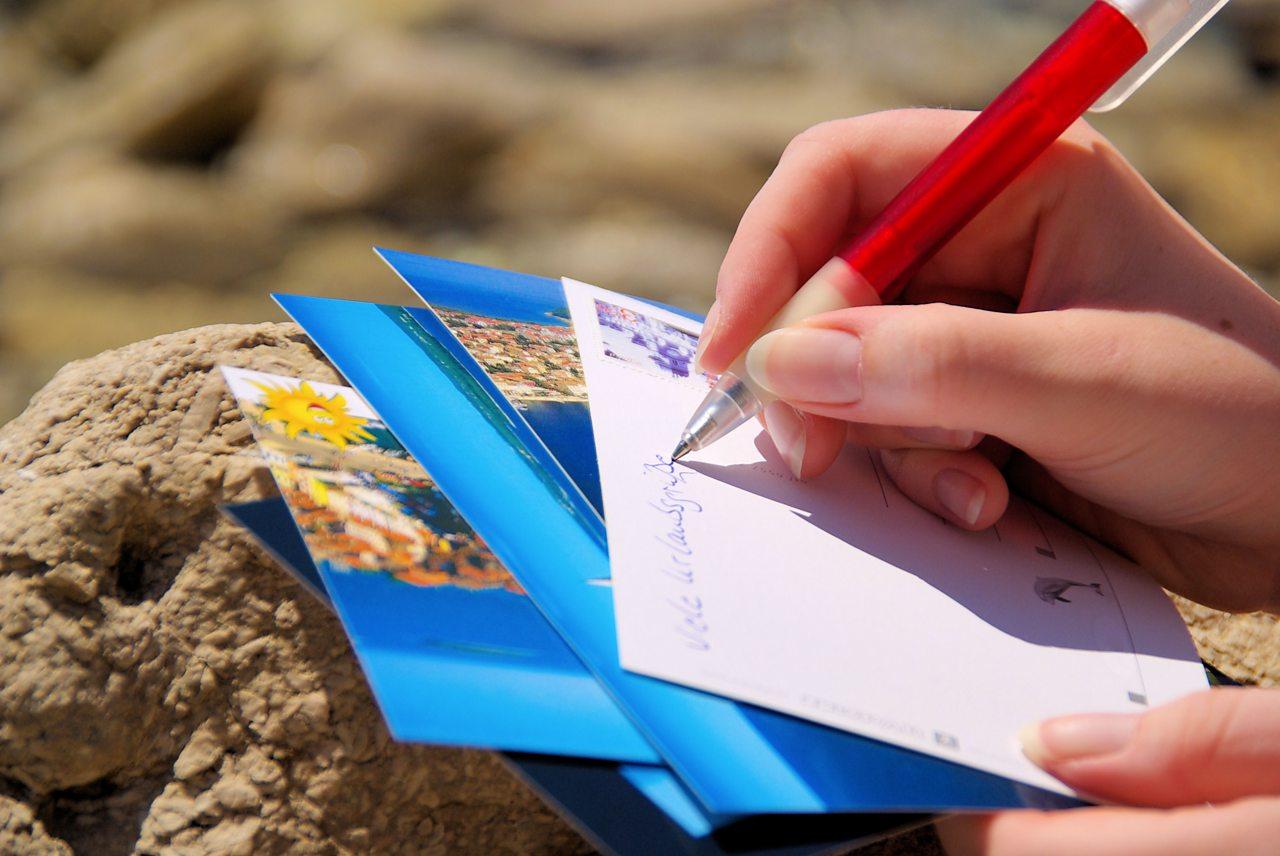 Person writing a postcard