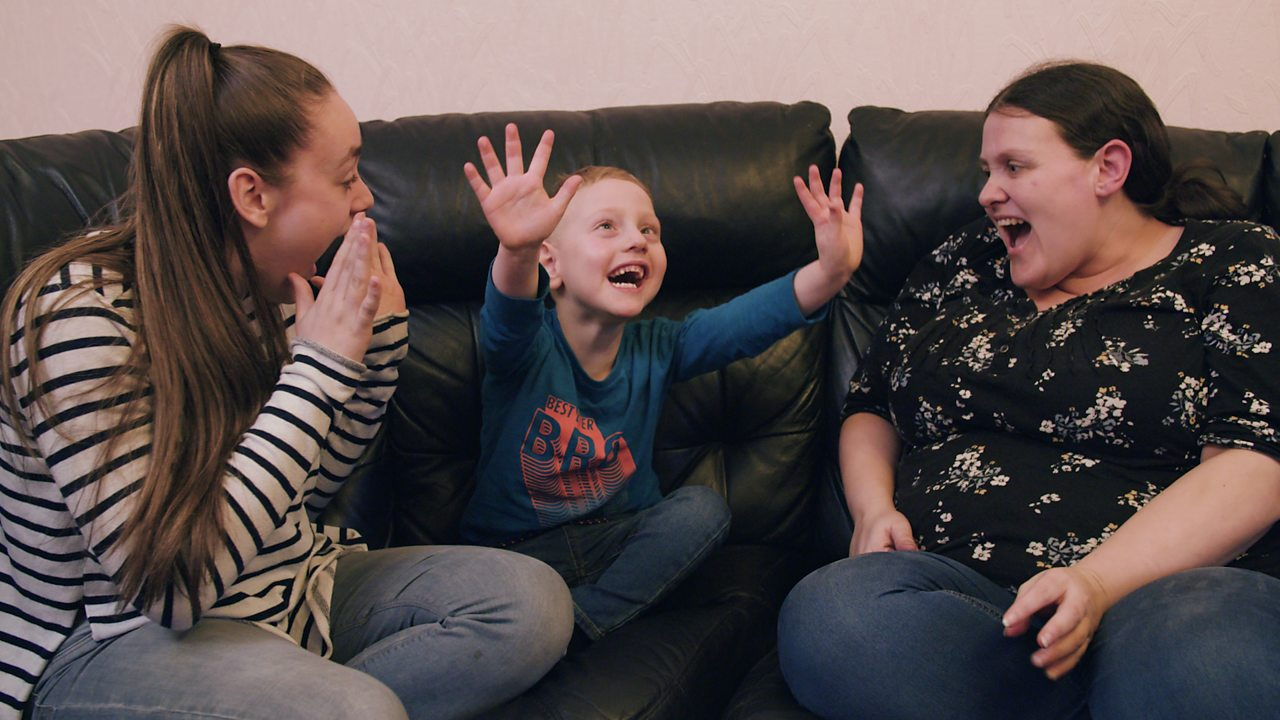 A little boy singing with his mum and older sister.