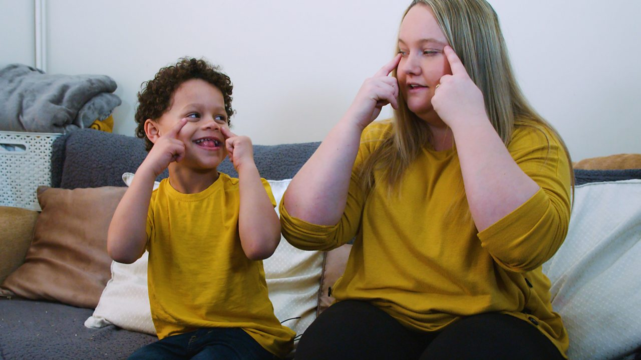 A little boy and his mum singing head, shoulders, knees and toes.
