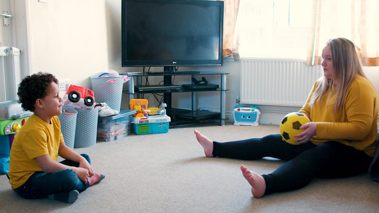 A mum and her son playing a ball rolling game.