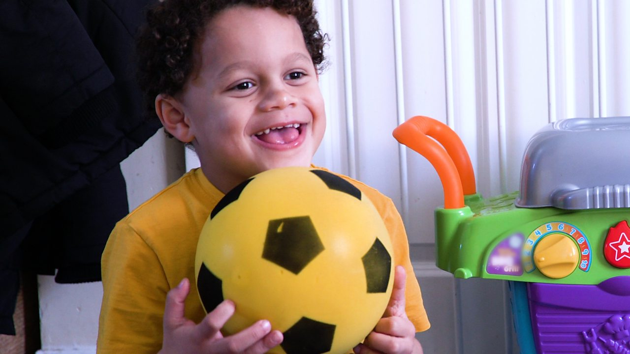 A little boy holding a ball with a big smile.