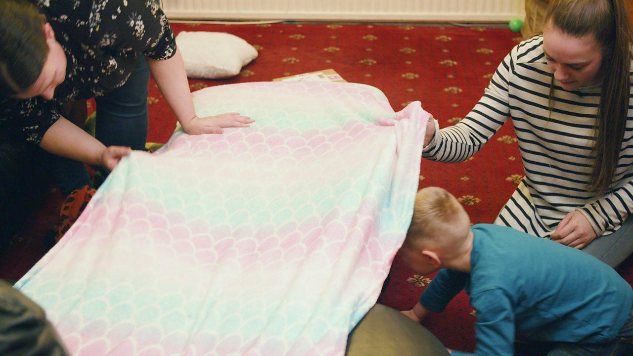 A little boy crawling under a blanket.