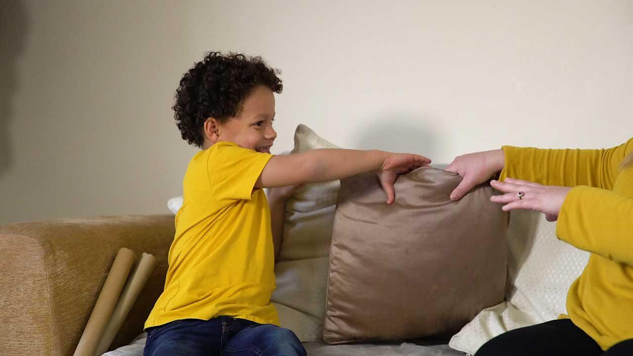 A little boy grabbing a pillow.