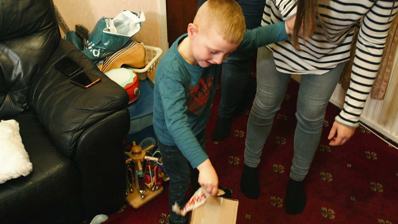 A little boy placing a cardboard box on the floor.