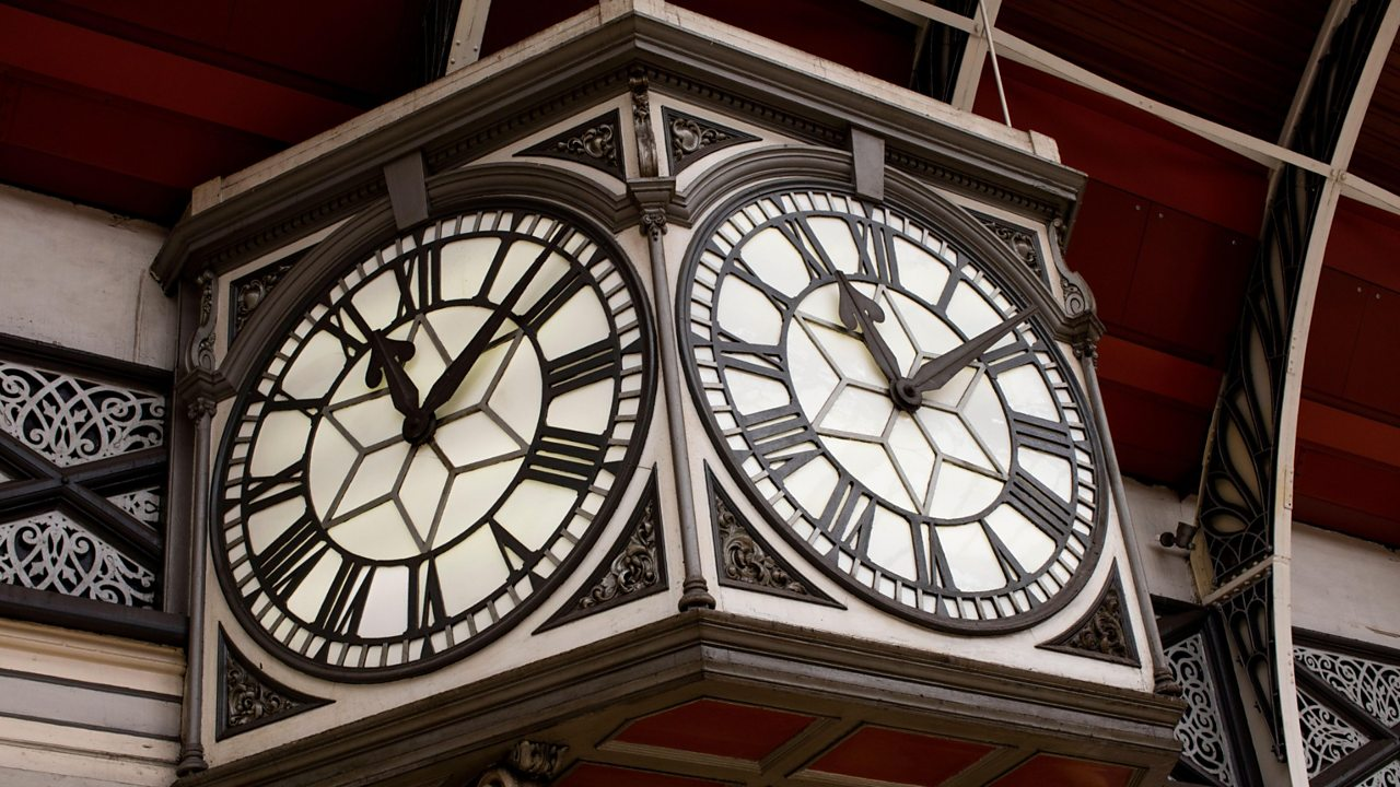 A photograph of an electric station clock.