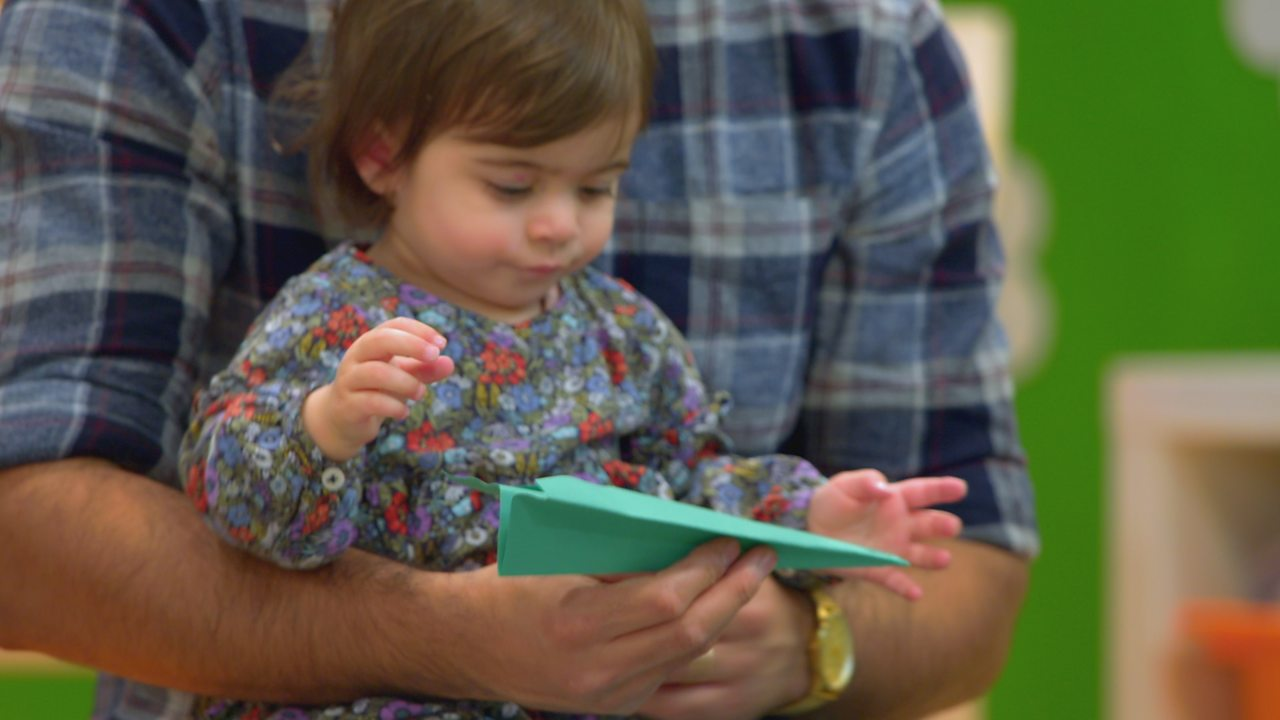 A parent coddles their baby while carrying a paper aeroplane
