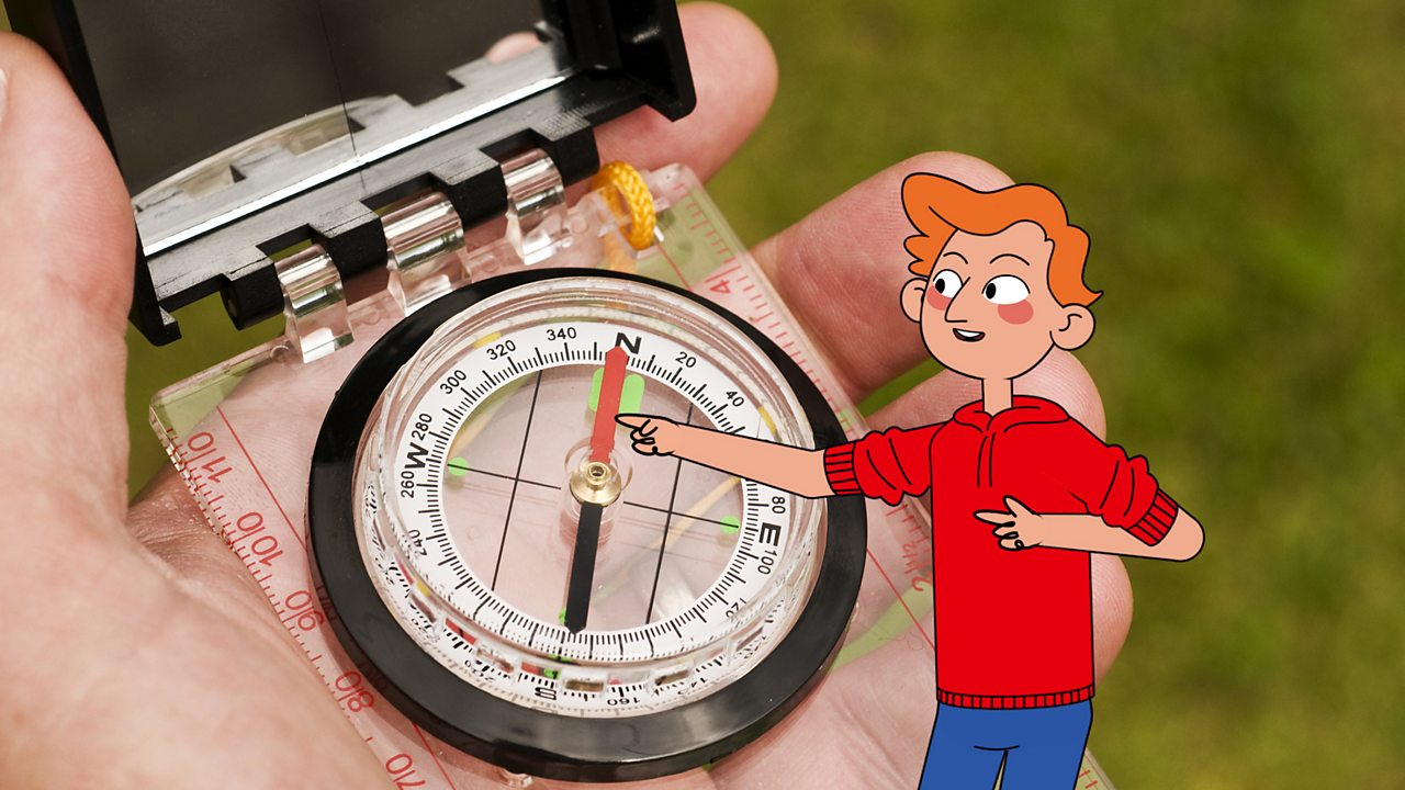 James is pointing at the red needle of a compass to show where north is