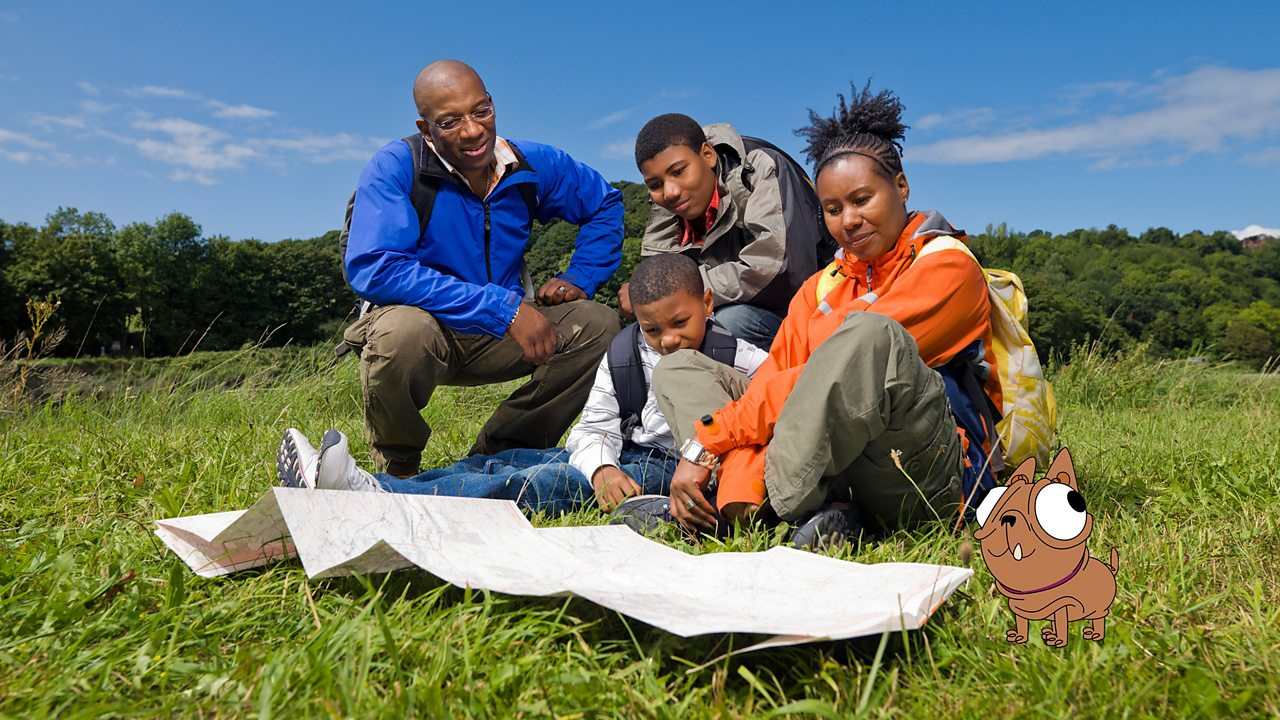 A family walking in the countryside is looking at a map of the local area