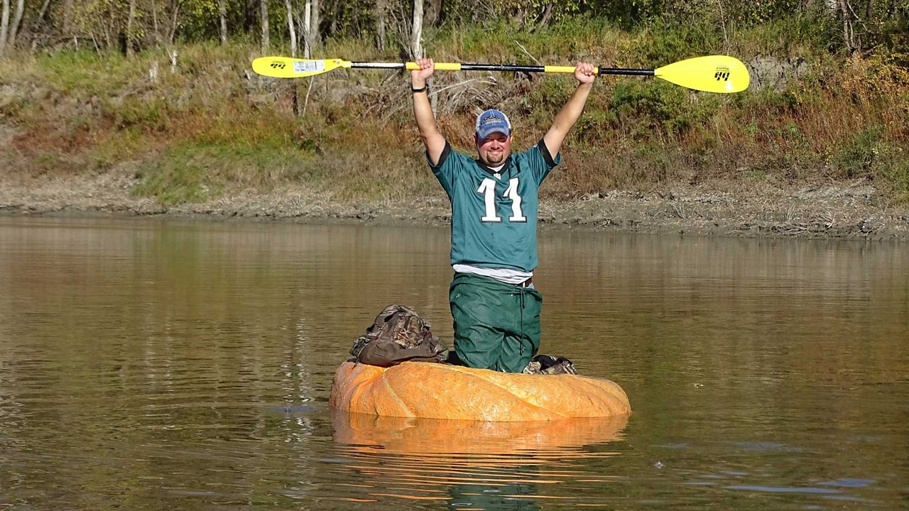 Rick Swenson standing in his pumpkin paddle boat