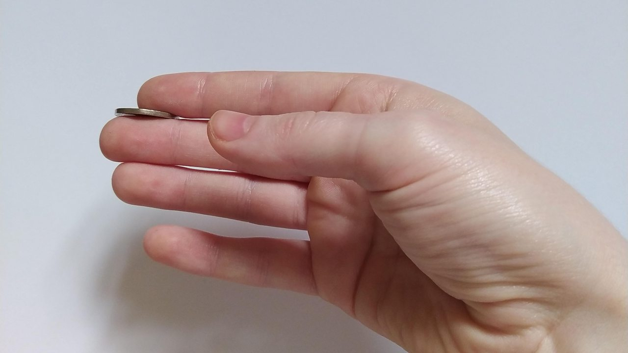 Close up of a hand holding a 20p piece between the index and middle finger.
