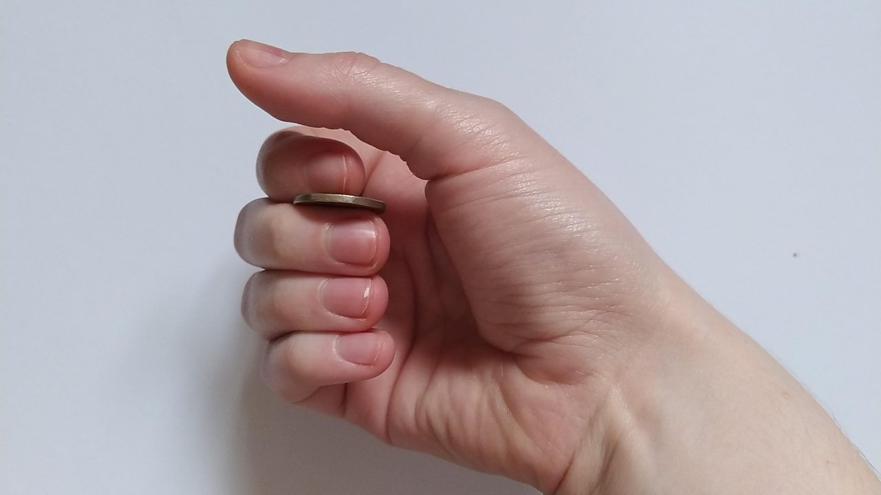 Close up of a hand holding a 20p piece between the index and middle finger, the fingers curled towards the thumb.