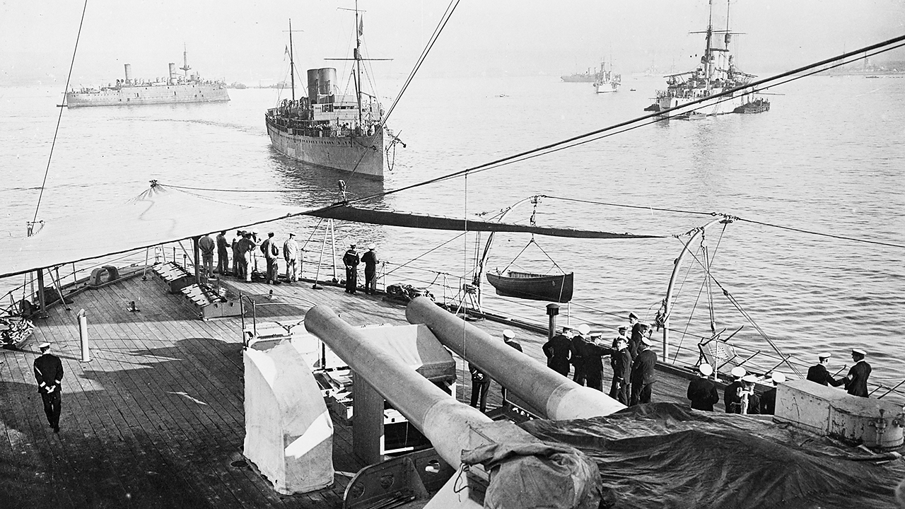 A photograph taken from onboard a battleship of World War One with naval officers looking out to sea with five naval ships at rest.