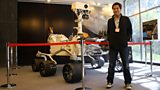 Kevin Fong standing next to a life size replica of the Curiosity Mars rover at NASA's JPL