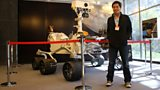Kevin Fong standing next to a life size replica of the Curiosity Mars rover at NASA's Jet Propulsion Laboratory