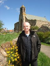 David Almond with St Mary's Church, Lindisfarne in the background