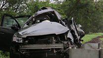 Crash investigator looks over car wreckage