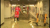 Staff and firefighters work to clear floodwater at Didcot Parkway