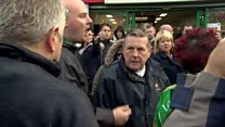 Priest confronted by angry protesters