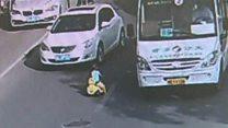 El momento en que un niño se mete con su auto de juguete en medio de una calle transitada en China