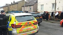 Armed police surround shot man's house
