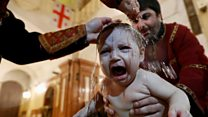 Babies dunked in water in mass baptism
