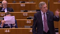 'He's lying' sign held behind Farage