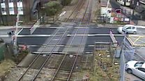 Driver swerves through level crossing