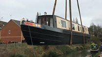 Narrowboat lifted on to canal