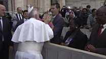 Young girl removes Pope's hat