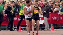 Exhausted marathon runner helped across line