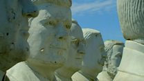 Giant presidents' statues crumble in field