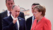 メルケル氏、プーチン氏に何かを言われ……その表情は「やれやれ」?