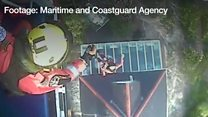 The coastguard helicopter crew winch people to safety