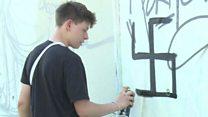 Berlin street artists tackle swastikas