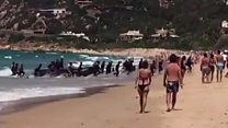 El impactante momento en que una patera llena de inmigrantes llega a playa española repleta de veraneantes