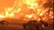 Wildfire rages by California highway