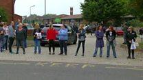 Parents form human barrier at school gate