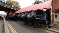 Lorry hits railway bridge and topples in to garden.