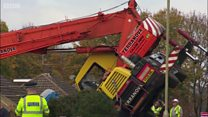 Driver trapped as crane falls on house