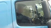 Driver on phone with foot on dashboard