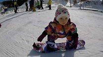 Девочка катается на сноуборде в один год