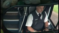 Driver on phone at wheel of holiday coach