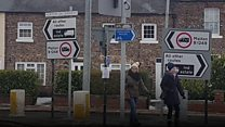 Town signs put up pointing opposite ways